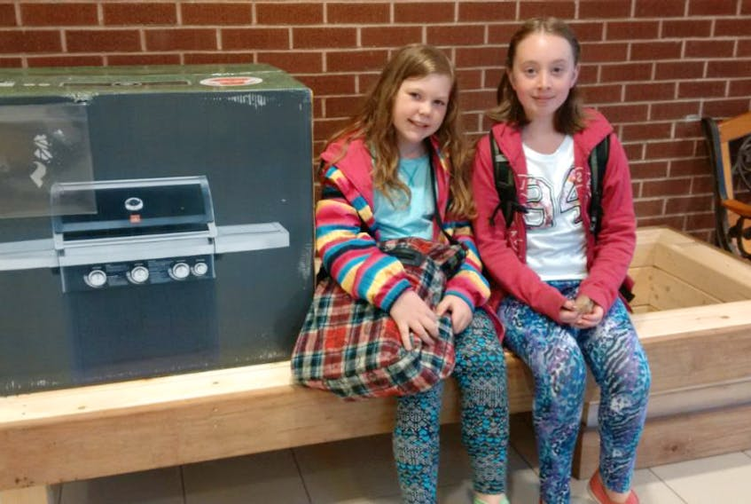 Gaspereau Valley Elementary School students Hannah Steadman-Griffiths, left, and Ava Nichols show off some of the items available at the fundraising auction on May 23, including a barbecue donated by the New Minas Atlantic Superstore and a planter bench donated by SRG Construction. All funds raised at the auction will go towards providing bonus activities for students at the school.