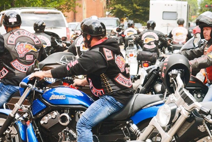 Members of the Red Devils motorcycle gang join members of the Hells Angels heading out from parking spots on Grafton Street in Charlottetown while on a tour of P.E.I. Friday. The group is based in Montreal, Que.
