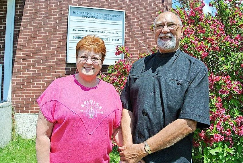 Rev. Lawrence D. Hartley and his wife Charlotte stand in front of the Highland AME Church. Rev. Hartley has restored ministry to the church that had been without a pastor for several years.