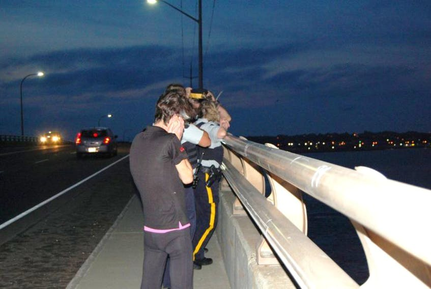 Passersby and police look over the side of the Hillsborough Bridge Wednesday evening after a woman apparently jumped from the bridge. She was rescued by boaters from a nearby marina and the Charlottetown Fire Services inshore rescue unit.