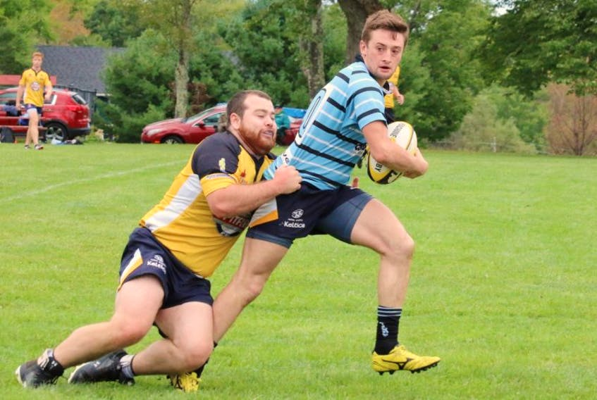 Jason Cookson holds on tightly as he attempts to tackle this Tars player.