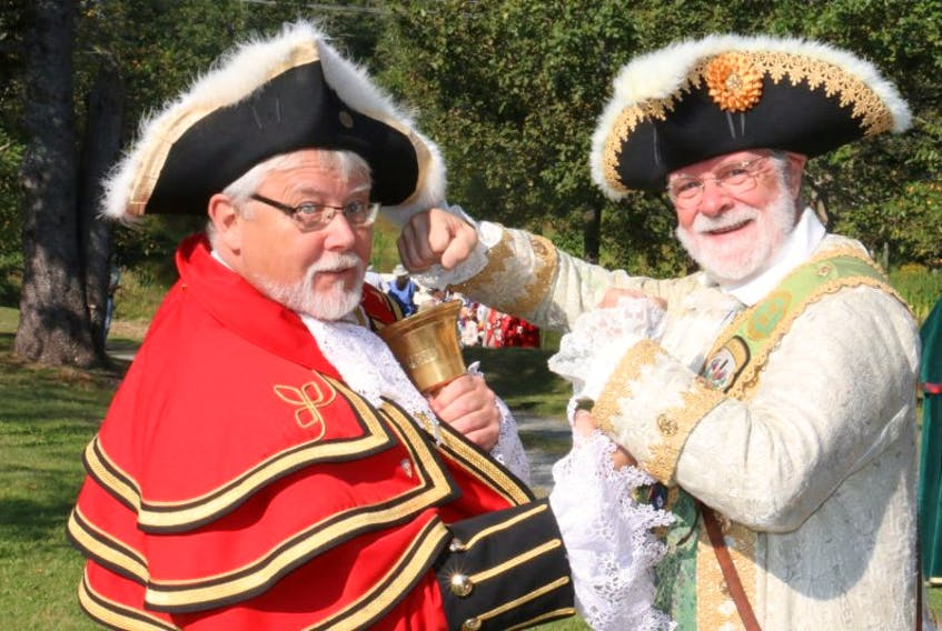 Kingston town crier Chris Whyman, left, and Windsor town crier Lloyd Smith joke around at the site of Lond Pond – the very place Windsor claims hockey originated.