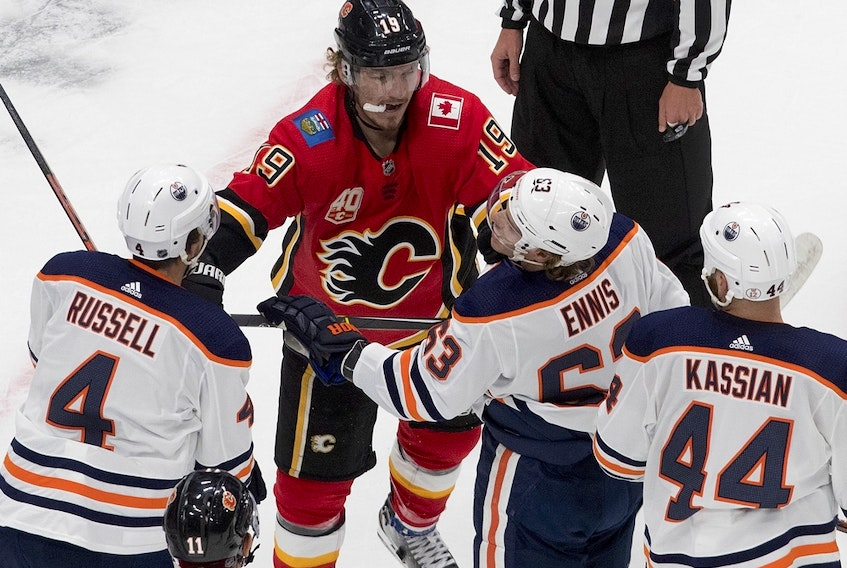 The Calgary Flames' Matthew Tkachuk roughs it up with Edmonton Oilers Kris Russell (4), Tyler Ennis (63) and Zack Kassian (44) during an exhibition game at Rogers Place on July 28, 2020.