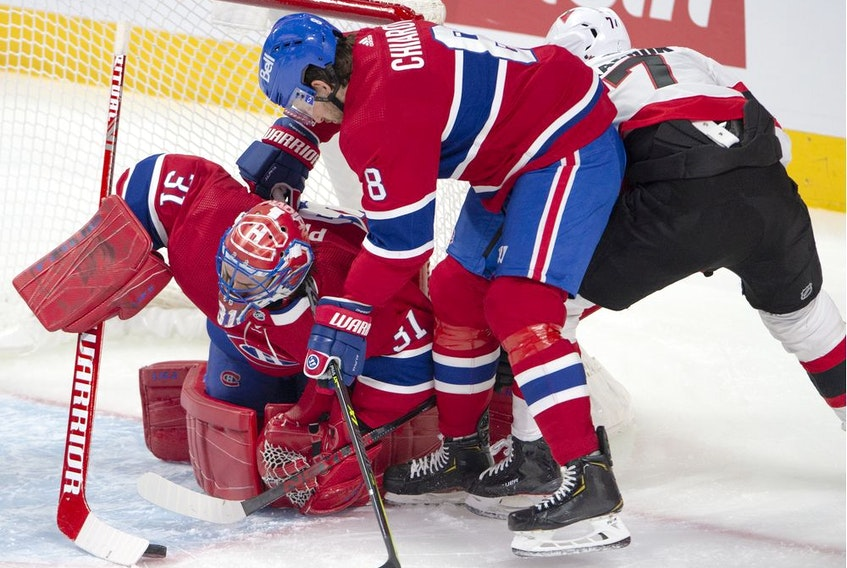 Canadiens goaltender Carey Price grabs a loose puck as Montreal defenceman Ben Chiarot and Senators' Brady Tkachuk battle for the rebound during the first period Tuesday night at the Bell Centre.
