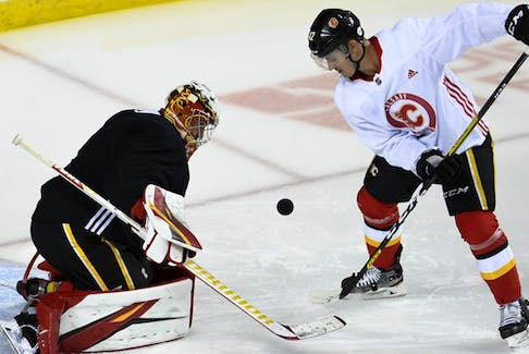 Calgary Flames goalie David Rittich and centre Glenn Gawdin keep an eye on the puck during a workout at the Scotiabank Saddledome on July 14, 2020. Candice Ward/USA TODAY Sports