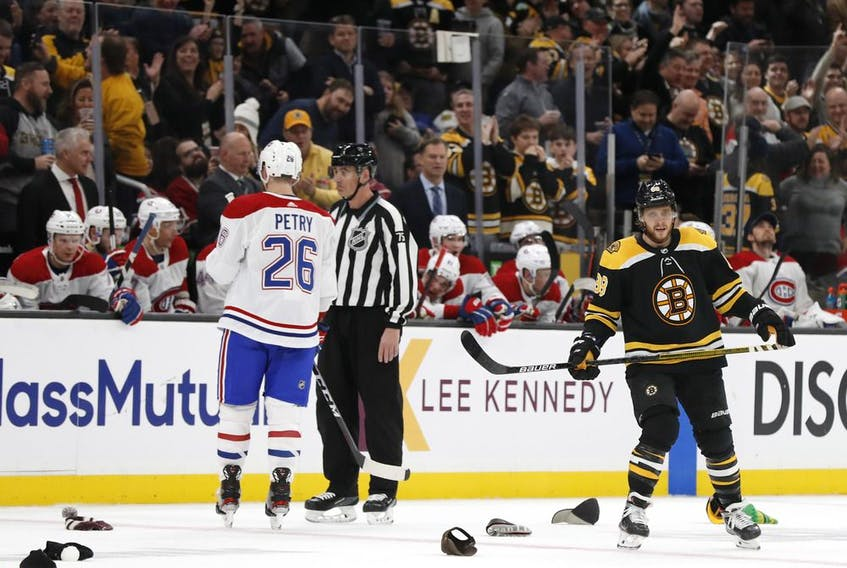 As hats litter the ice in honour of his third goal of the night, Bruins' David Pastrnak skates past Canadiens' Jeff Petry Wednesday night in Boston.