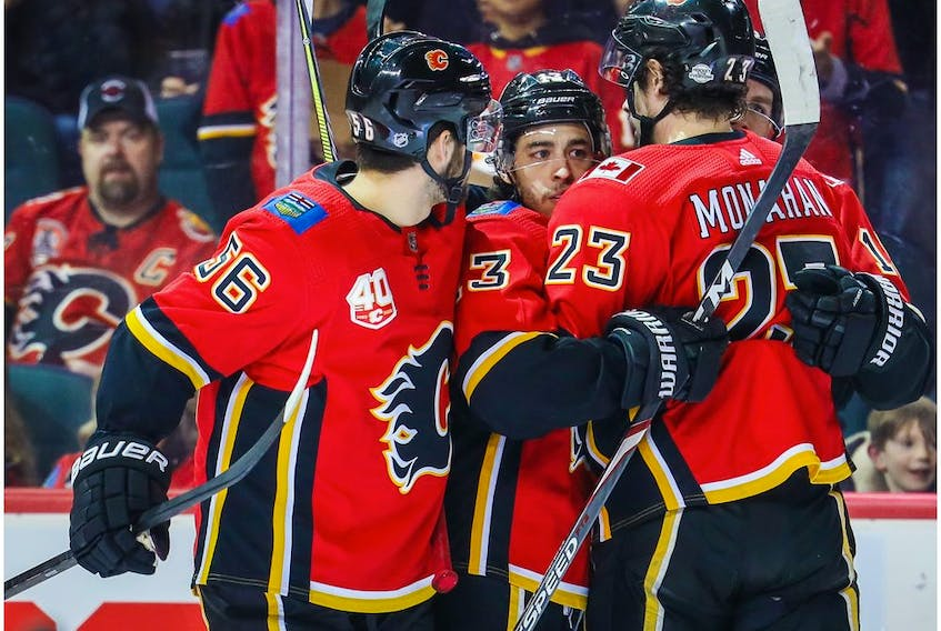 Mar 6, 2020; Calgary, Alberta, CAN; Calgary Flames left wing Johnny Gaudreau (13) celebrates with teammates after scoring a goal against the Arizona Coyotes during the first period at Scotiabank Saddledome. Mandatory Credit: Sergei Belski-USA TODAY Sports ORG XMIT: USATSI-406039