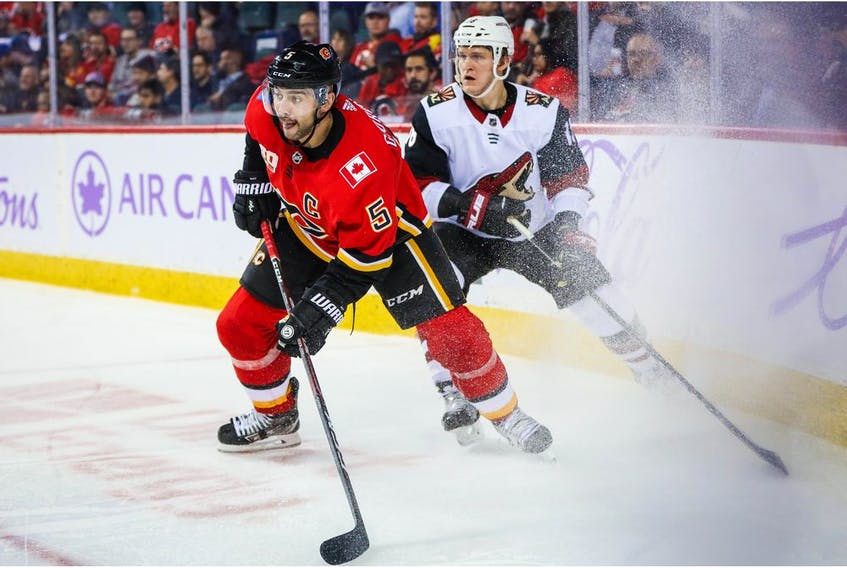 Nov 5, 2019; Calgary, Alberta, CAN; Calgary Flames defenseman Mark Giordano (5) and Arizona Coyotes left wing Christian Dvorak (18) battle for the puck during the second period at Scotiabank Saddledome. Mandatory Credit: Sergei Belski-USA TODAY Sports ORG XMIT: USATSI-405224