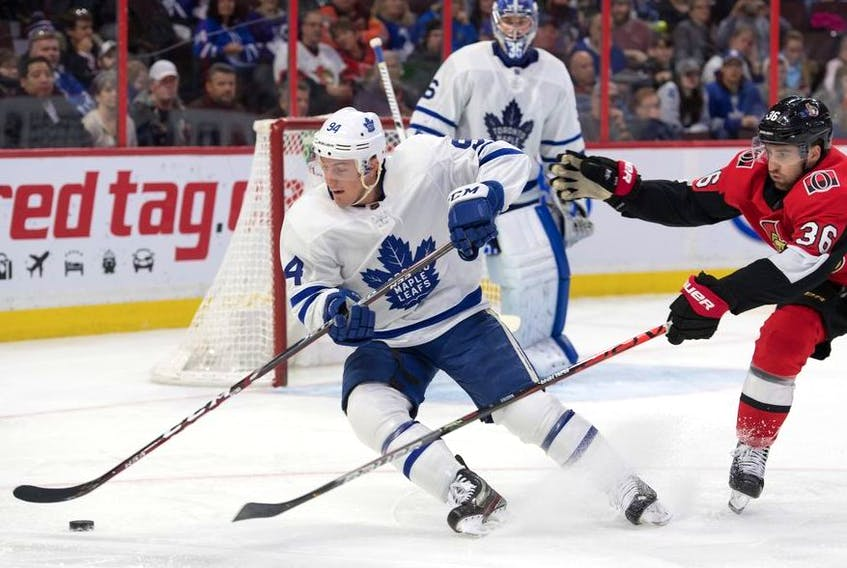 Toronto Maple Leafs defenseman Tyson Barrie skates with the puck away from Ottawa Senators center Colin White in the second period at the Canadian Tire Centre.