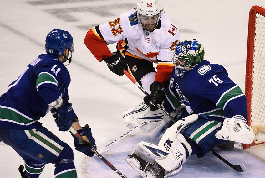 Vancouver Canucks goaltender Michael DiPietro (75) and forward Jonah Gadjovich (41) defend against Calgary Flames forward Justin Kirkland (52) during the second period at Save-On-Foods Memorial Centre.