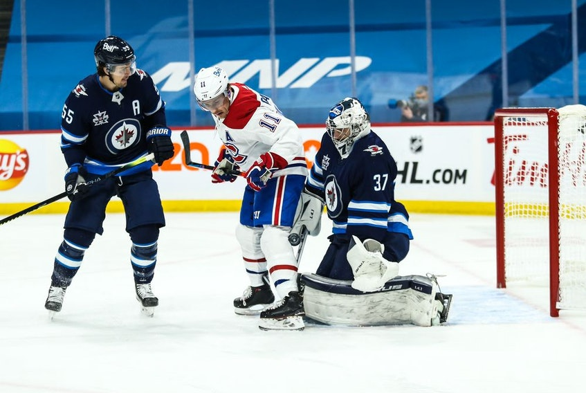 Winnipeg Jets goalie Connor Hellebuyck (37) makes a save despite being screened by Montreal Canadiens forward Brendan Gallagher (11) during the first period at Bell MTS Place. Mandatory Credit: Terrence Lee-USA TODAY Sports