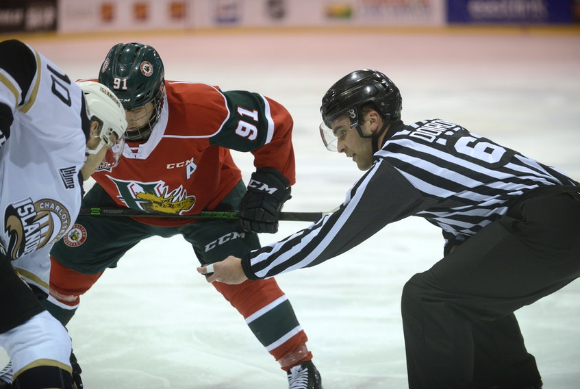 Linesman Tanner Doiron, right, prepares to drop the puck during a faceoff between Charlottetown Islanders centre Brett Budgell, left, and Halifax Mooseheads centre Elliot Desnoyers during a recent Quebec Major Junior Hockey League game at the Eastlink Centre.
