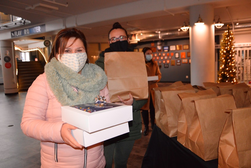 Sandra Kanchuk, left, and Angela Bresson, both of Seaside Communications, pick up their Good Cheer Holiday Box at the Joan Harriss Cruise Pavilion on the Sydney waterfront on Friday. The initiative to boost the morale of local businesses was spearheaded by the Cape Breton Partnership and the Cape Breton Regional Chamber of Commerce. The organizations raised money through sponsorships to defray part of the cost for each holiday box valued at $200. There were 70 made available to local companies at a cost of $50 per box. It included a platter of snacks from Flavor Creative Catering, local brews and ciders from Breton Brewing and Island Folk Cider House, as well as holiday decorations from Walter's Party Rentals. The Good Cheer program replaced the formal Winter reception normally held in downtown Sydney in early December. It could not take place this year due to government-imposed crowd restrictions as a result of the COVID-19 pandemic. CHRIS SHANNON • CAPE BRETON POST