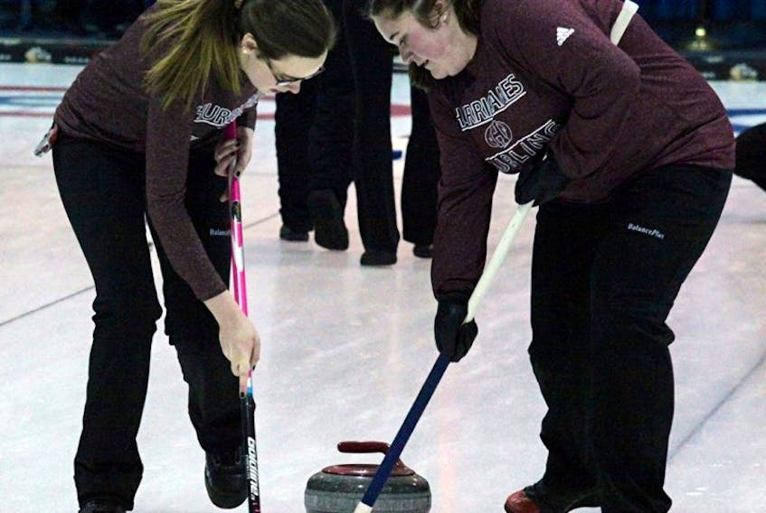 Bethany Dauphinee, left, and Breanna Huntley sweep a stone during the CCAA National Championships in Olds, Alta., March 24. The two represented Holland College and had a 2-5 record.