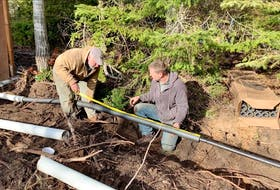 Steve and homeowner Brad installing an insulated and heated water line on a site with too little soil for frost protection. Brad says the fully encased, 150-foot-long installation has no noticeable effect on his electricity bill.