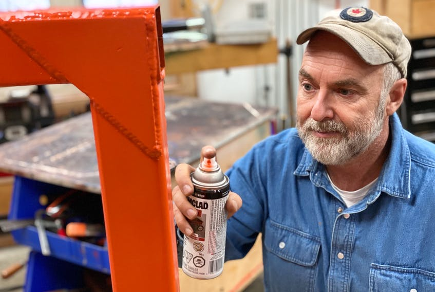 Steve Maxwell applies rust paint to a newly made metal item in his shop. With a little bit of prep work, today's best metal paints do not peel.