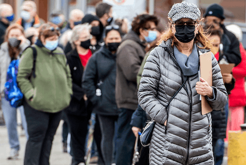 People line up outside of a Shoppers Drug Mart in Toronto for their COVID-19 vaccine on Thursday. Experts say the vaccine offers hope for a quicker return to normal life.