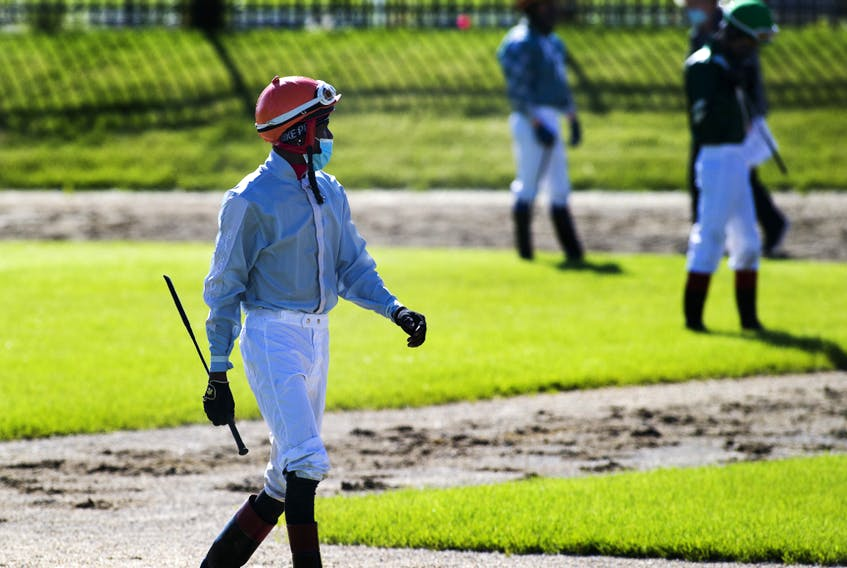 Jockeys enter the paddock wearing masks before the first race on opening day of the season for Century Mile Racetrack on Sunday, June 21, 2020. No fans were allowed in the stands, just jockeys, horses and trainers.