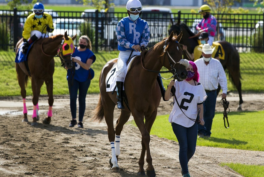 Jockeys prepare to leave the paddock on opening day of the season for Century Mile Racetrack on Sunday, June 21, 2020. No fans were allowed in the stands, just jockeys, horses and trainers.