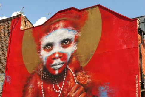 During the first Cities of Hope street art convention in 2016, Manchester artist Dale Grimshaw used his Globalization, 'Free West Papau' and '2 Worlds' themes to paint the side of a Spear Street building with the image of a young Papua New Guinea child wearing body paint and facing a harsh future. (Ian Robertson)