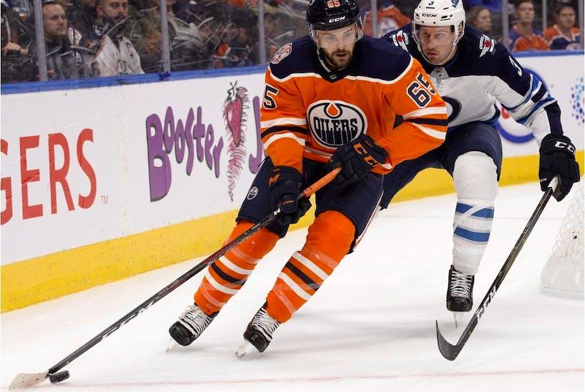 Edmonton Oilers forward Cooper Marody battles the Winnipeg Jets defenceman Tucker Poolman during pre-season NHL action at Rogers Place in Edmonton on Sept. 20, 2018.