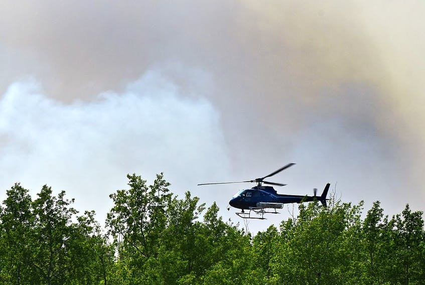 A helicopter flys tree-top level ahead of wildfire crews doing controlled burn ignition operation approximately three kilometres southwest of High Level where about 5,000 residence were evacuated from the Chuckegg Creek fire, May 23, 2019. Ed Kaiser/Postmedia