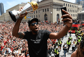 Kawhi Leonard takes a selfie holding his playoffs MVP trophy as he celebrates during the 2019 Toronto Raptors Championship parade in Toronto on June 17, 2019.