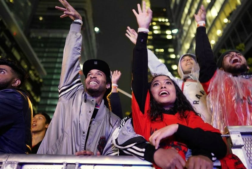 In this file photo taken on June 10, 2019 Toronto Raptor fans cheer during a street party in Jurassic Park, outside of Scotiabank Arena in Toronto, Ontario, during Game 5 of the NBA Championships against the Golden State Warriors. -