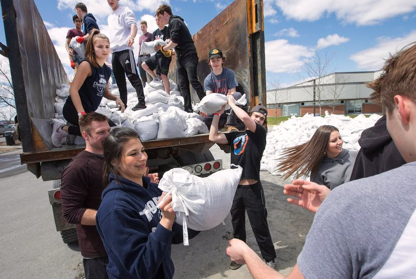 Students and faculty from West Carleton High School pitch in and fill a mountain of sandbags at the campus, to be picked up by residents and the city.  Wayne Cuddington / Postmedia
