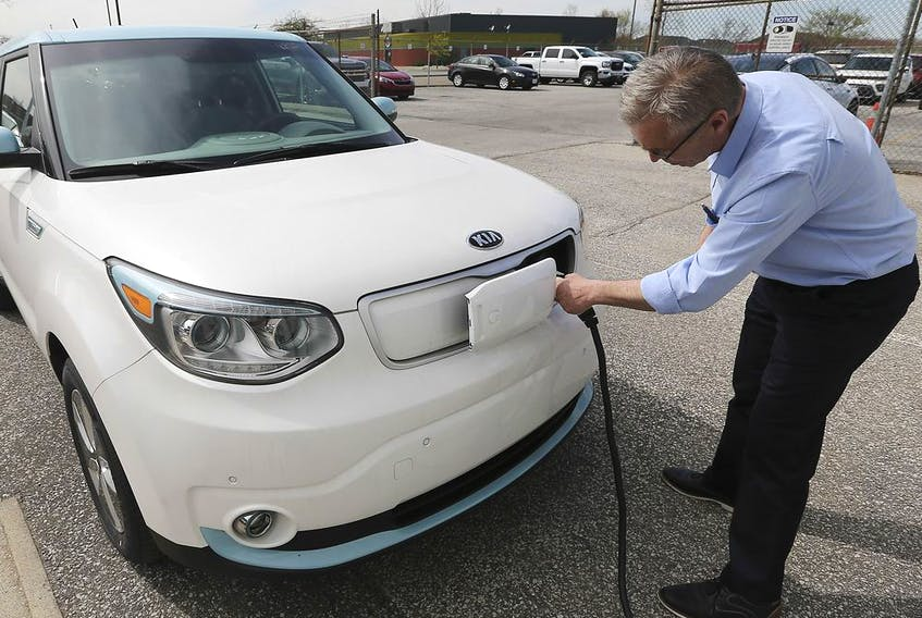 Dan Campeau, a sales agent with Gus Revenberg Kia in Windsor is shown with a 2019 KIA EV Soul Luxury electric car on Wednesday, April 24, 2019.