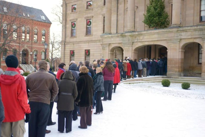 Islanders line up for the New Year's Levee held at Province House Thursday.