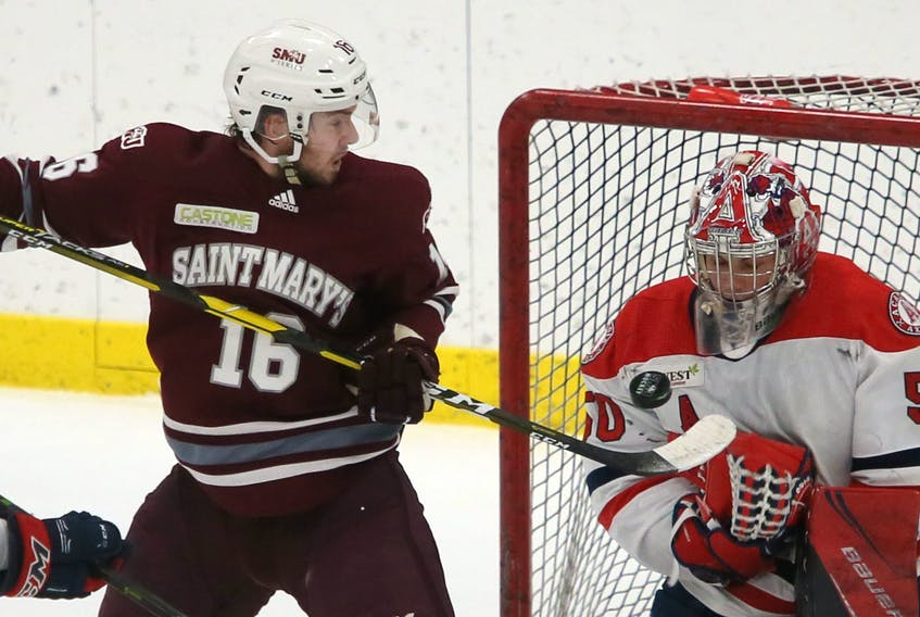 Saint Mary's Huskies forward Keith Getson and Acadia Axemen goalie Logan Flodell eye the puck during an AUS men's hockey league game in Halifax on Wednesday. (TIM KROCHAK/Chronicle Herald)