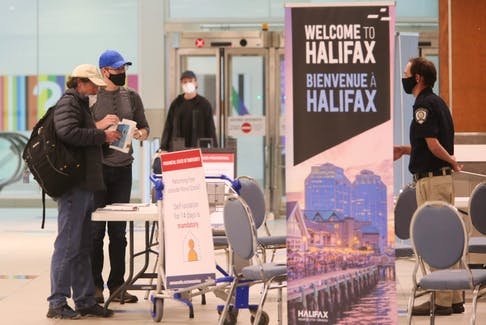 Air passengers who just arrived on a flight from St. John's speak to a member of Nova Scotia heath enforcement staff in the baggage area of Halifax Stanfield International Airport on Thursday, July 2, 2020.