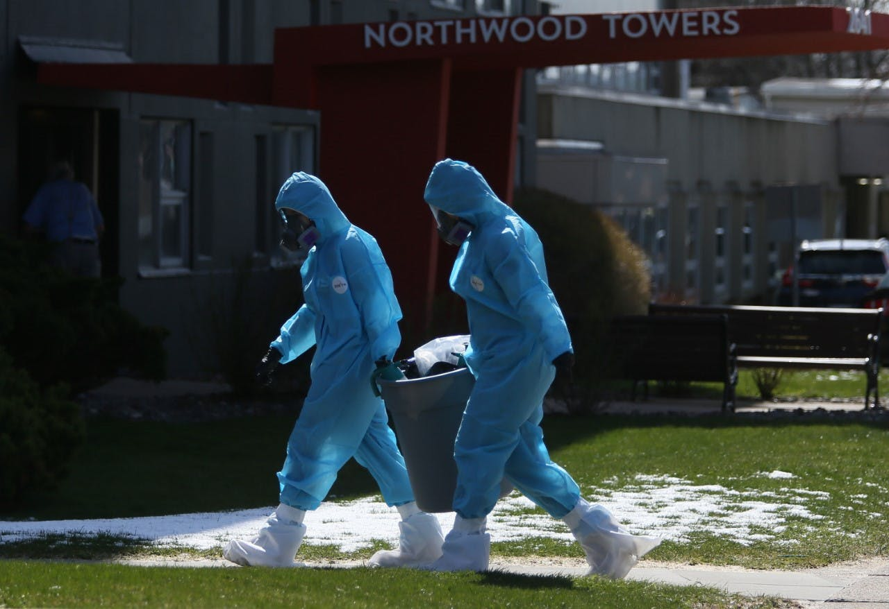 Workers in full personal protective equipment remove a trash can from Northwood Towers in Halifax on Wednesday, April 29, 2020. Northwood has had the most COVID-19 related deaths in the province, 21 out of 27 deaths that have occurred up until today.