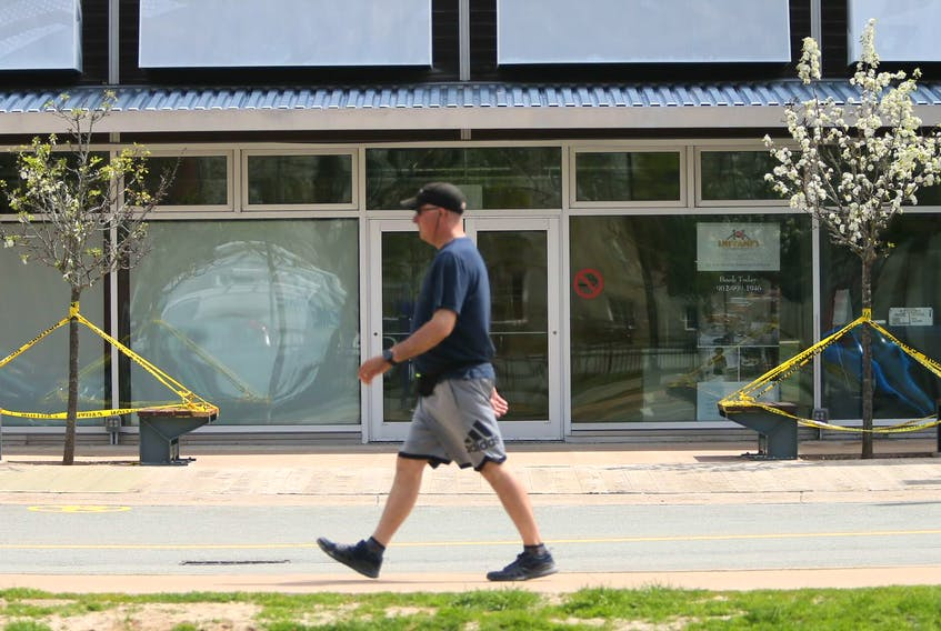A man strolls past benches taped off to prevent sitting, outside the Halifax Seaport Farmers' Market, also closed, in Halifax, Wednesday, May 27, 2020.