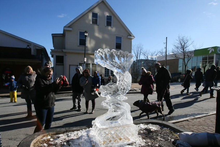 Visitors take photos of some of the ice sculptures completed during the Downtown Dartmouth Ice Festival in Dartmouth on Saturday, Feb. 8, 2020.
