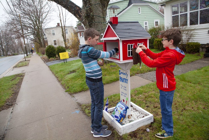Rylan, 13, and Bren DeCoste, 8, put non-perishables and face masks into the School House pantry on the front lawn of their Dartmouth home Monday, May 4, 2020. Their mother Jennifer said that the food is going out quickly these days.