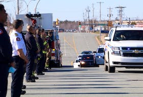 Police, firefighters and other emergency personnel line Garland Avenue in Dartmouth as the body of an RCMP officer is transported to the Dr. William D. Finn Centre for Forensic Medicine for an autopsy Sunday evening, April 19, 2020.