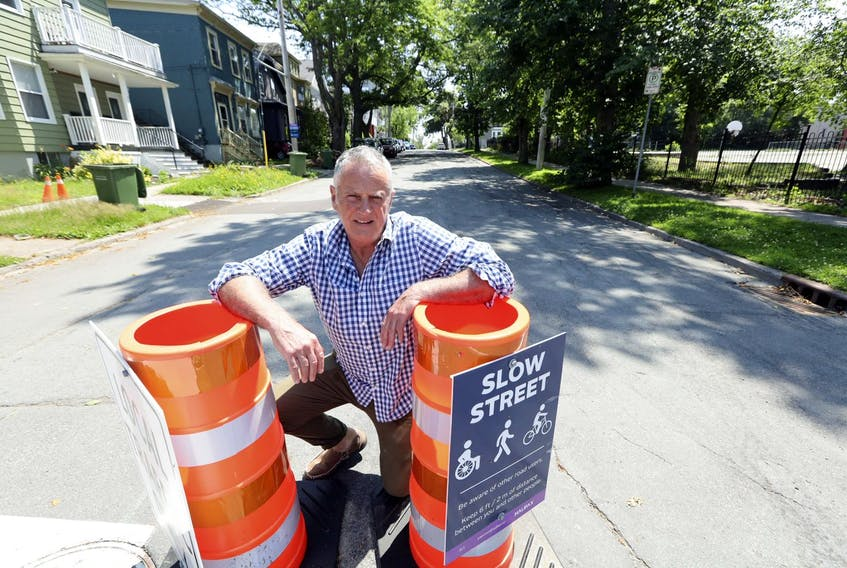 Columnist John DeMont poses for a photo on Walnut Street with pylons designating the residential street as a 'slow street'.