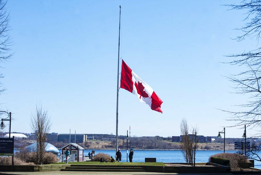 The giant flag near the wave sculpture on the Halifax waterfront flies at half-mast on Tuesday morning,, April 21, 2020 in memory of the victims of the weekend's mass shootings.