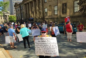 A protester's sign calls for a reduction in class sizes when Nova Scotia public schools reopen in September. The woman was part of a rally by a group of teachers and parents concerned about the safety of the Liberal government's back-to-school plans, held at the entrance to government offices on Granville Street in Halifax on Monday, August 10.