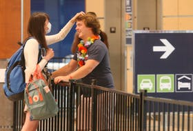 Chloe Puddister plays with the hair of her boyfriend, Hayden Goss, as the couple reunites in the baggage area of Halifax Stanfield International Airport on Thursday, July 2, 2020 after spending the last three-and-a-half months apart. Chloe had just arrived from a flight from St. John's.