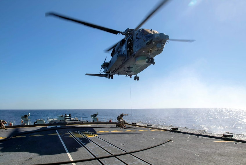 Air detachment members aboard HMCS Fredericton couple a fueling hose to the hoist cable of a CH-148 Cyclone helicopter during Operation Reassurance at sea Feb. 15, 2020. - Cpl. Simon Arcand / Canadian Forces via Reuters