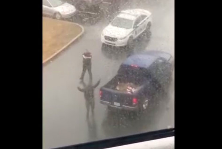 A Halifax Regional Police officer points his gun at a man with his hands in the air in this screengrab from video. The confrontation happened Friday, March 26, 2021, outside an apartment building at 210 Wentworth Dr. in Halifax. - Screengrab / DeRico Symonds' Facebook page
