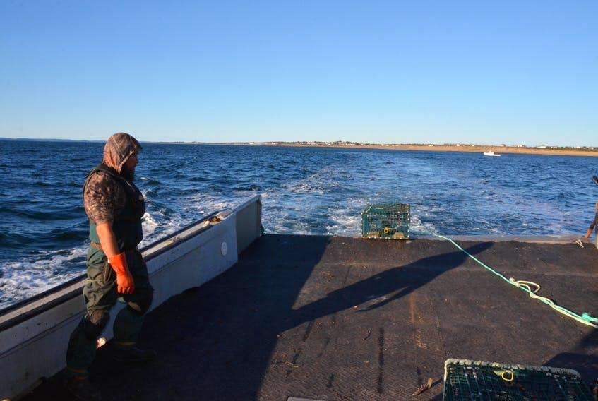 Lance Bernard watches the last of a string of traps go over the stern of the Lady Carol 1 as part of the moderate livelihood fishery. (AARON BESWICK PHOTO)