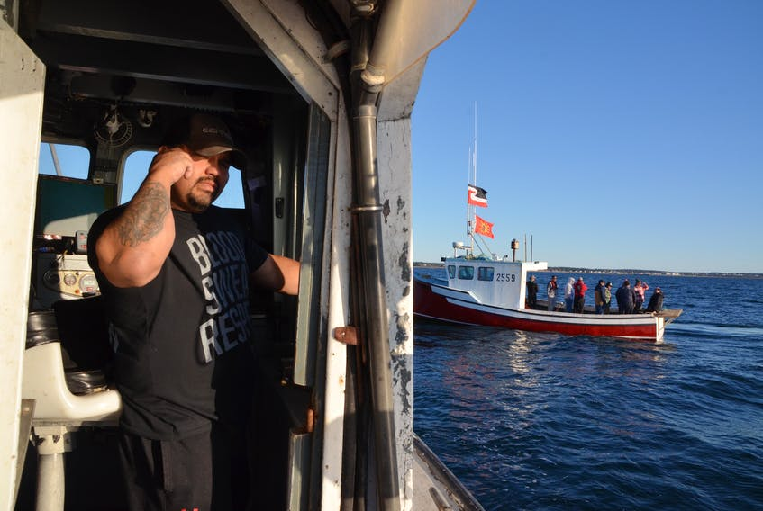 Terence Augustine aboard his vessel, The Lady Carol 1, looking for traps on Sunday evening that had been seized by commercial fisherment. (AARON BESWICK PHOTO)