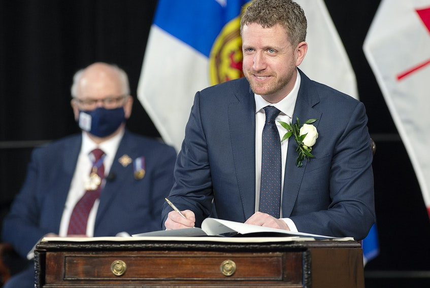 Nova Scotia Premier Iain Rankin, accompanied by Lt.-Gov. Athur LeBlanc, left, signs his oath of office in Halifax on Tuesday, Feb. 23, 2021. Rankin replaces Stephen McNeil who  announced last summer he was stepping down after 17 years in politics. THE CANADIAN PRESS/Andrew Vaughan