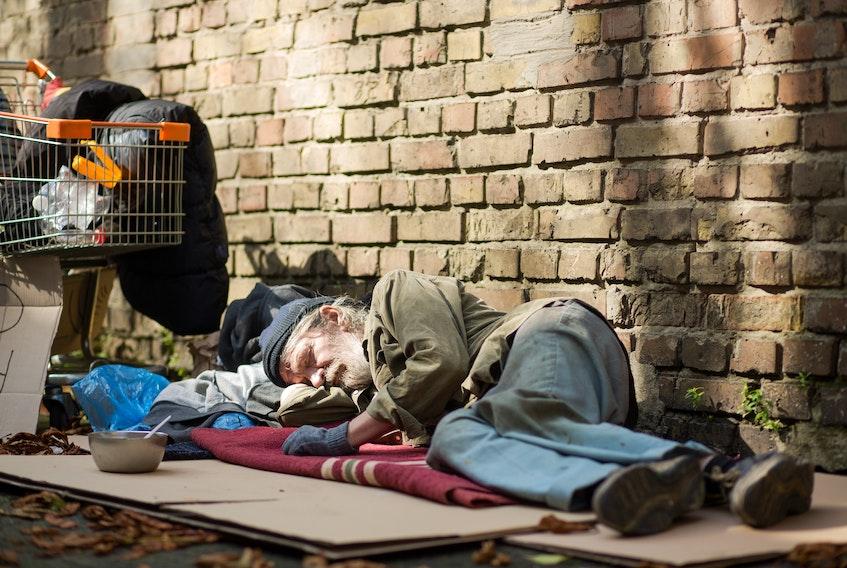 A sleeping homeless man lying on cardboard. STOCK IMAGE