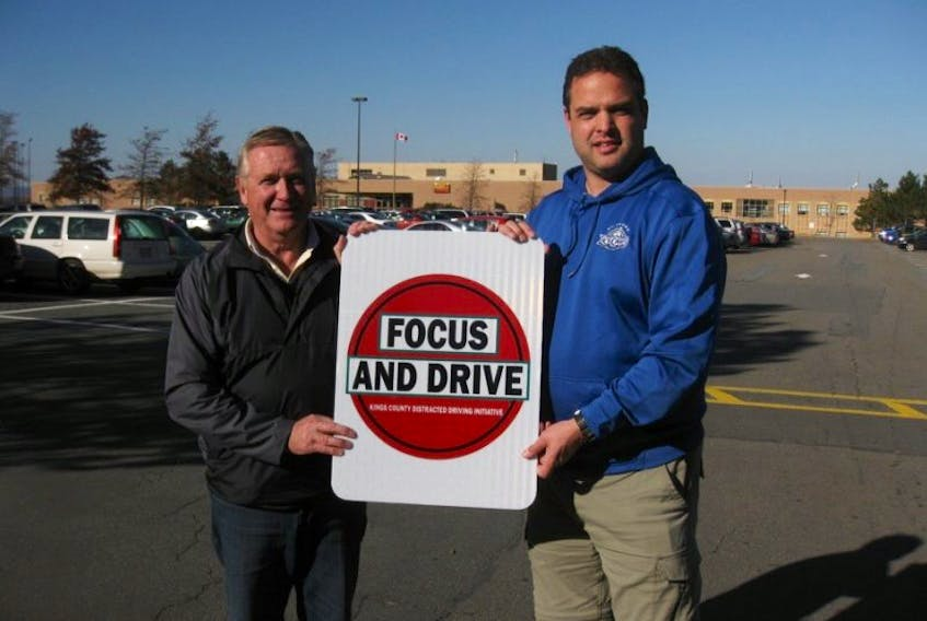 Paul Gates, left, and RCMP Sgt. Andrew Buckle were out putting up signs recently warning of distracted driving.