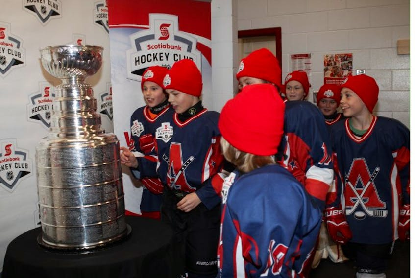 Members of the Acadia atom AA hockey team get up close and personal with the Stanley Cup during its Nov. 25 visit to the Andrew H. McCain Arena in Wolfville.
